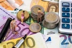 Zabawkarscy ludzie siedzą na euro monecie z kalkulatora, pióra i euro rachunkami, fotografia royalty free