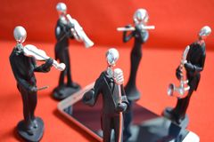 Zabawkarscy muzycy wokoło telefonu komórkowego na czerwonym tle Fotografia Stock