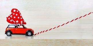Zabawkarscy samochodowi dostarcza serca dla walentynki ` s dnia przeciw tłu kolorowy bokeh Obrazy Royalty Free