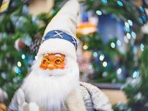 Zabawkarska Święty Mikołaj pozycja przeciw świątecznej jaskrawej iluminującej miękkiej części skupiał się bokeh tło zdjęcie stock