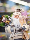 Zabawkarska Święty Mikołaj pozycja przeciw świątecznej jaskrawej miękkiej części skupiał się tło obraz stock