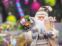 Zabawkarska Święty Mikołaj pozycja przeciw świątecznej jaskrawej miękkiej części skupiał się tło zdjęcia royalty free