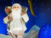 Zabawkarska Święty Mikołaj pozycja przeciw gwiaździstemu zmrokowi - błękitny tło fotografia royalty free