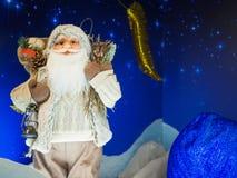 Zabawkarska Święty Mikołaj pozycja przeciw gwiaździstemu zmrokowi - błękitny tło obrazy stock
