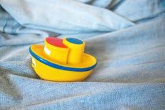 Zabawkarska żółta gumowa łódź w fałdach błękitny drelichowy morze Statek Obraz Stock