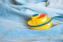 Zabawkarska żółta gumowa łódź w fałdach błękitny drelichowy morze Statek Obrazy Stock