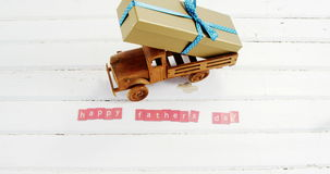 Zabawkarska ciężarówka z prezentem i szczęśliwymi ojca dnia blokami układał na drewnianej desce zbiory wideo