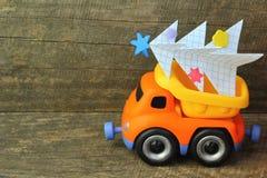 Zabawkarska ciężarowa przewożenie ręcznie robiony papieru choinka przeciw szorstkiemu drewnianemu tłu Boczny widok Choinka przetw Zdjęcie Stock