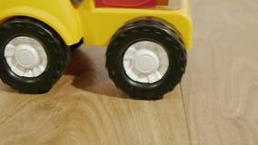 Zabawkarska kolor żółty ciężarówka jedzie w pokoju na brown drewnianej podłoga zbiory