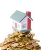 Zabawkarska mały dom pozycja na rozsypisku monety. Fotografia Royalty Free