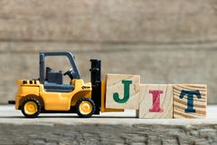 Zabawkarski żółty forklift chwyta listu blok J uzupełniać słowa JIT skrót W sam raz zdjęcia royalty free