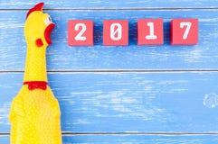 Zabawkarski żółty shrilling kurczak i Szczęśliwy nowy rok 2017 liczb na r Zdjęcia Stock