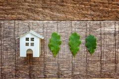 Zabawkarski dom i zieleń dębowi liście na drewnianym tle Obrazy Royalty Free