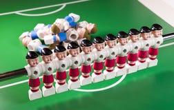 Zabawkarski gracza futbolu stojak na boisku piłkarskim, kilka postacie spadał, kłamstwo Pojęcie nadmiar, niepotrzebni ludzie zdjęcia royalty free
