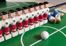 Zabawkarski gracza futbolu stojak na boisku piłkarskim, kilka postacie spadał, kłamstwo Pojęcie nadmiar, niepotrzebni ludzie obrazy royalty free