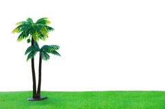 Zabawkarski kokosowy drzewo na trawie z odosobnionym na białym tle Obraz Royalty Free
