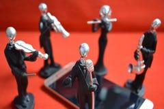 Zabawkarski mężczyzna i muzycy wokoło telefonu komórkowego na czerwonym tle Zdjęcia Stock
