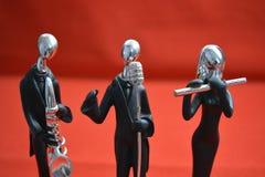 Zabawkarski mężczyzna z mikrofonem i muzykami na czerwonym tle Zdjęcia Royalty Free