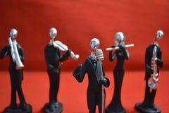 Zabawkarski mężczyzna z mikrofonem i muzykami na czerwonym tle Obraz Stock