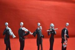 Zabawkarski mężczyzna z mikrofonem i muzykami na czerwonym tle Fotografia Royalty Free