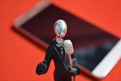 Zabawkarski mężczyzna z mikrofonem i telefonem komórkowym na czerwonym tle Zdjęcia Royalty Free