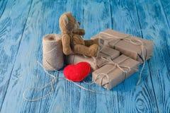 Zabawkarski niedźwiedź i niektóre papierowi pakuneczki zawijający na drewnianym stole Obrazy Stock