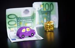 Zabawkarski samochód, euro i złota teraźniejszość na czerni, Ostrość na samochodzie zdjęcia stock