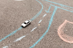 Zabawkarski samochód na asfalcie kredy malujący drogowi ocechowania righthand ruch, obracanie i pasek, zdjęcia royalty free