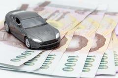 Zabawkarski samochód na pieniądze odizolowywającym na białym tle Obraz Royalty Free