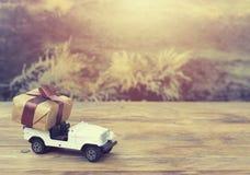 Zabawkarski samochód niesie zawijającego prezenta pudełko, natury tło Obraz Stock