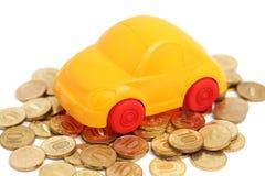 Zabawkarski samochodu stojak na stosie monety (odizolowywać) Obraz Stock