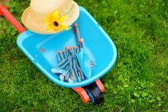 Zabawkarski wheelbarrow, children ogrodowe rękawiczki i ogrodowi narzędzia, Fotografia Royalty Free