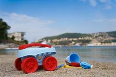 Zabawki kłamają na piasku plażowy pobliski morze Zdjęcie Stock