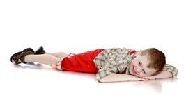 Zabawy chłopiec lying on the beach na podłoga fotografia stock
