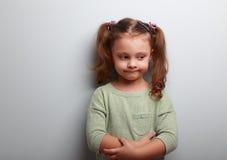Zabawy główkowania dzieciaka dziewczyna patrzeje na błękit ściany tle zdjęcie royalty free
