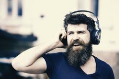 Zabawy, radości i muzyki pojęcie, Brodaty modnisia mężczyzna jest ubranym duże słuchawki słucha muzyka Młody człowiek śpiewa alon fotografia royalty free