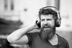 Zabawy, radości i muzyki pojęcie, Brodaty modnisia mężczyzna jest ubranym duże słuchawki słucha muzyka Młody człowiek śpiewa alon obrazy royalty free