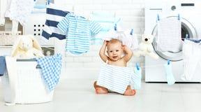 Zabawy szczęśliwa chłopiec myć odzieżowego i śmiechy w pralni