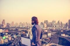Zachodni biznesmen patrzeje Bangkok miasto przy zmierzchem Zdjęcie Royalty Free