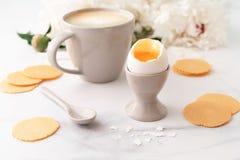Zacht-gekookt ei met liquide oranje dooier in ceramisch eierdopje, kop van koffie en dunne knapperige graanspaanders op achtergro stock afbeelding