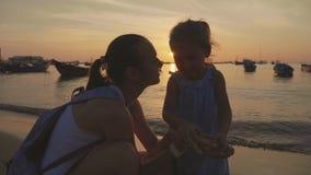 Zacht portret van jonge moeder met haar weinig dochter op het strand bij zonsondergang stock footage