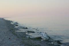 Zacht roze hemel die regelmatig in het blauwe overzees overgaan Kustgolven royalty-vrije stock afbeeldingen
