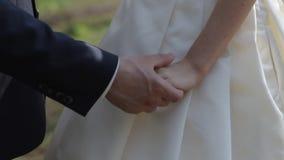 Zacht verbonden handen van een onlangs-gehuwd paar stock video