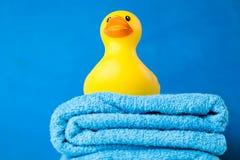 Zachte blauwe handdoeken en een stuk speelgoed eend Stock Foto's