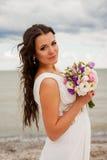 Zachte bruid met een boeket op het strand. Stock Afbeelding