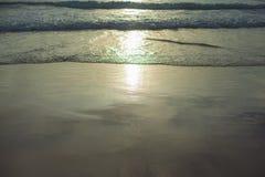 Zachte golf van het overzees op zandige strandzonsondergang Stock Foto