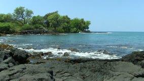 Zachte Golven op Zwart Lava Rock Shore With Trees op Achtergrond stock videobeelden