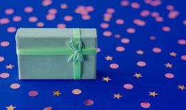 Zachte groene giftdoos op donkerblauwe achtergrond stock afbeeldingen