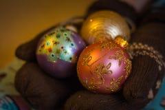 In zachte handen waarop de warme vuisthandschoenen gekleed zijn ligt de bal van een Nieuwjaar voor de viering van een Nieuwjaarbo stock afbeeldingen