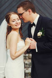 Zachte modieuze sgroom en bruidholdingshanden en het glimlachen op royalty-vrije stock fotografie